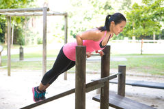Woman doing push up on bar in outdoor exercise park Stock Photos