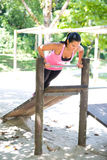 Woman doing push up on bar in outdoor exercise park. Beautiful woman doing push up on bar in outdoor exercise park royalty free stock image