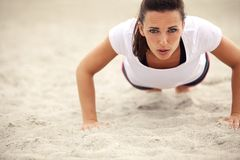 Woman Doing Push Up Exercise on the Beach. Push-ups fitness woman doing pushups outside on beach. Fit female sport model girl training crossfit outdoors Royalty Free Stock Images