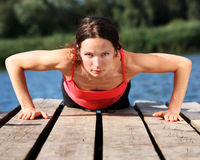 Woman doing push-ups. Sporty young woman doing push-ups outdoors. Shot was taken with polarized filter stock photo