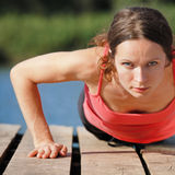 Woman doing push-ups. Strong sporty female doing push-ups outdoors royalty free stock photos