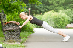 Woman doing push-ups. On bench in urban fitness exercise Royalty Free Stock Images