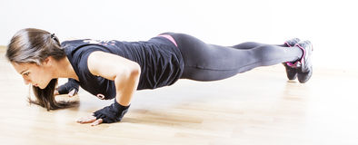 Woman doing push ups. Young woman doing push ups Royalty Free Stock Photo