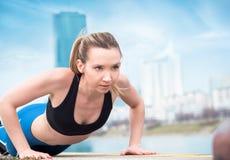 Woman doing push ups. Athletic woman exercising royalty free stock image