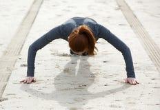 Woman doing push ups at beach royalty free stock image