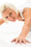 Woman doing push-ups exercises on white floor Stock Photography
