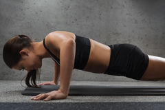 Woman doing push-ups in gym Stock Image