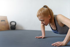 Woman doing push-ups in gym. Healthy lifestyle, slim body this s Stock Image