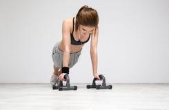 Woman doing push ups at gym. Young beautiful woman doing push ups at gym Royalty Free Stock Photos