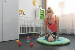 Woman doing push ups at home while playing with her little baby royalty free stock image
