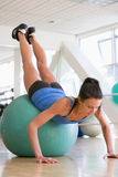 Woman Doing Push Ups On Swiss Ball At Gym Stock Photos