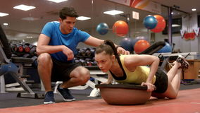 Woman doing push ups with trainer. In high quality 4k format stock video footage