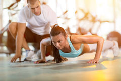 Woman doing push ups under supervision of a trainer Stock Photography
