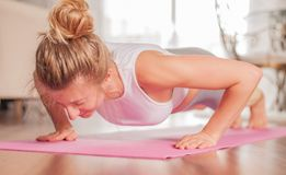 Woman doing push-ups on yoga mat at home. Fitness girl doing pushups on exercise mat royalty free stock image
