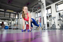 Woman doing pushup exercise with dumbbell in a gym Stock Photos