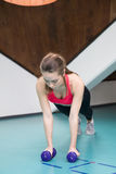 Woman doing pushup exercise with dumbbell in a gym Stock Photo