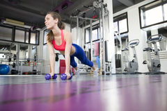 Woman doing pushup exercise with dumbbell in a gym Stock Image