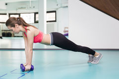 Woman doing pushup exercise with dumbbell in a gym Royalty Free Stock Photography