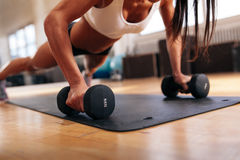 Woman doing pushups on dumbbells Stock Images
