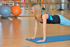 Woman doing pushups in gym Stock Photos