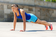 Woman doing pushups outdoor. Royalty Free Stock Images