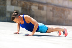 Woman doing pushups outdoor. Royalty Free Stock Image