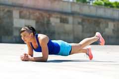 Woman doing pushups outdoor. one leg up. Royalty Free Stock Images