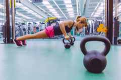 Woman doing pushups over kettlebells in crossfit Stock Images