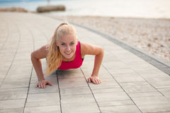 Woman doing pushups on a path near a sea Stock Images