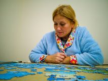 Woman doing puzzle in quiet house with a blue dressing gown stock photos