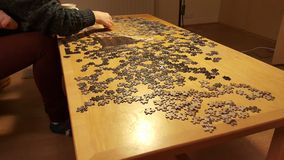 Woman doing puzzle on wooden table Royalty Free Stock Photo