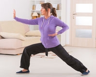 Woman doing qi gong tai chi exercise. Beautiful woman doing qi gong tai chi exercise at home Royalty Free Stock Photo