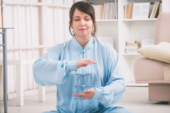 Woman doing qi gong tai chi exercise. Beautiful woman doing qi gong tai chi exercise or reiki wearing professional, original Chinese clothes at home Stock Image