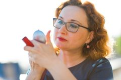 Woman doing quick make up outside royalty free stock images