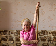 Woman doing rehab exercises with a stick at his home. Stock Images