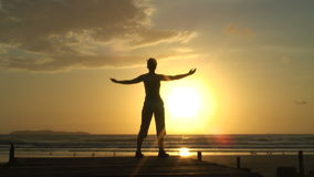 Woman doing relaxation exercises at sunrise
