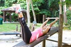 Woman doing reverse crunches in outdoor park. Stock Photography