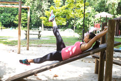 Woman doing reverse crunches in outdoor park. Sporty woman doing reverse crunches in outdoor park royalty free stock image