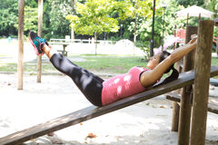 Woman doing reverse crunches in outdoor park. Sporty woman doing reverse crunches in outdoor park stock images