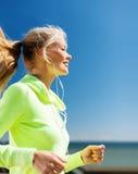Woman doing running outdoors Stock Photos