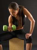 Woman doing seated dumbbell curl. Photo of an attractive female doing a dumbbell curl while sitting Stock Images
