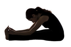 Woman doing seated forward bend pose in yoga stock photo