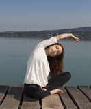 Woman doing seated side bend during yoga outdoors. Caucasian woman is doing side body stretch outdoors Stock Image
