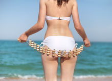 Woman doing self massage. Young slim woman doing self anti cellulite massage on the beach royalty free stock photography