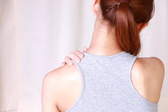 Woman doing self shoulder massage Stock Photo