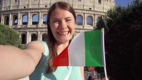 Woman doing selfie near Colosseum in Rome, Italy. Teenage girl waving Italian flag in slow motion stock video
