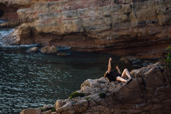 Woman doing selfie using selfie stick. young girl lies on a rock, on a background of rocks and lake. Woman doing weird selfie using selfie stick. young girl royalty free stock photos