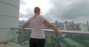 Woman doing shoulder exercises on the balcony. Hong Kong, China stock video