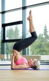 Woman doing shoulderstand on mat in gym Royalty Free Stock Images