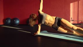 Woman doing a side plank for abdominal workout on blue mat. This Video about fitness. Sunset light